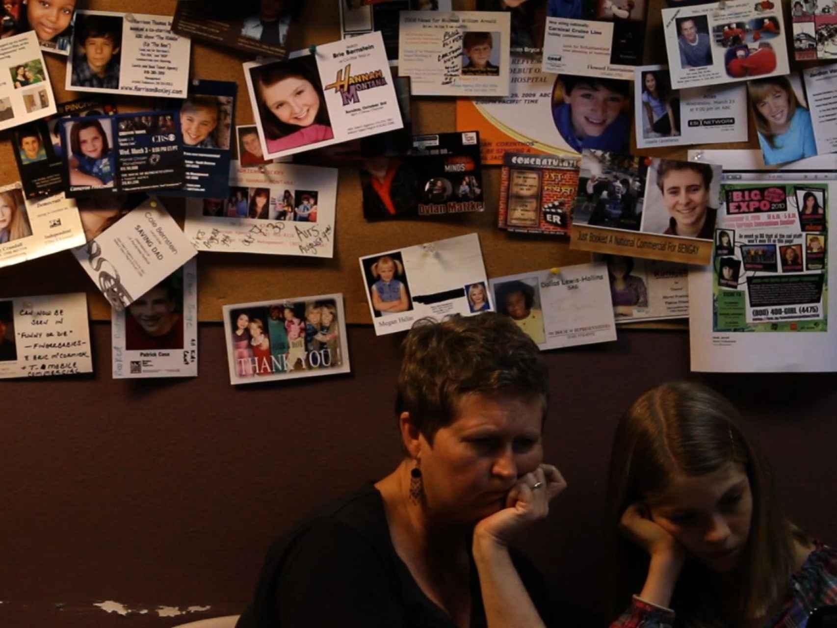 Madre e hija,en la sala de espera de una agencia.